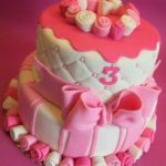 piętrowy tort z kokardą i różyczkami