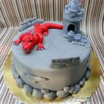 tort z czerwonym smokiem  na szarym zamku